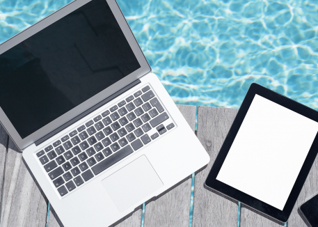 computer, tablet, and phone on deck next to pool
